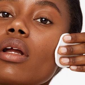 model uses cotton pad to rub same hydrating milk onto cheeks