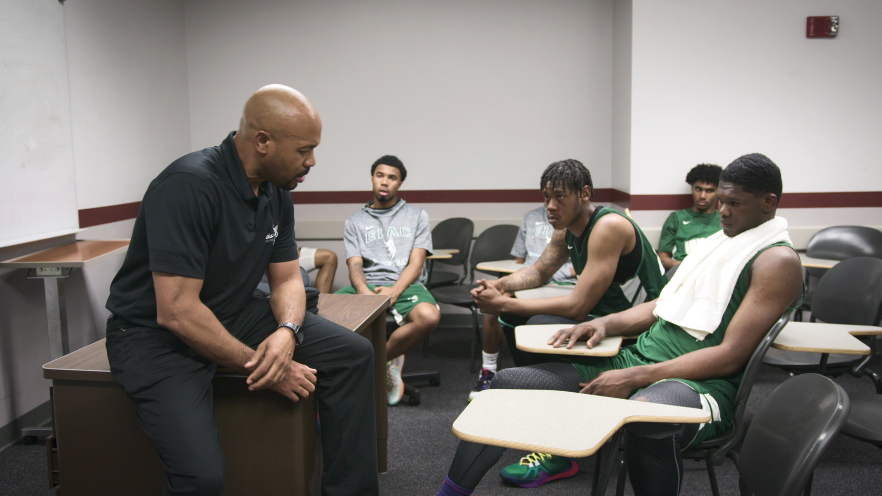 Basketball players sitting at desks in a room with a coach