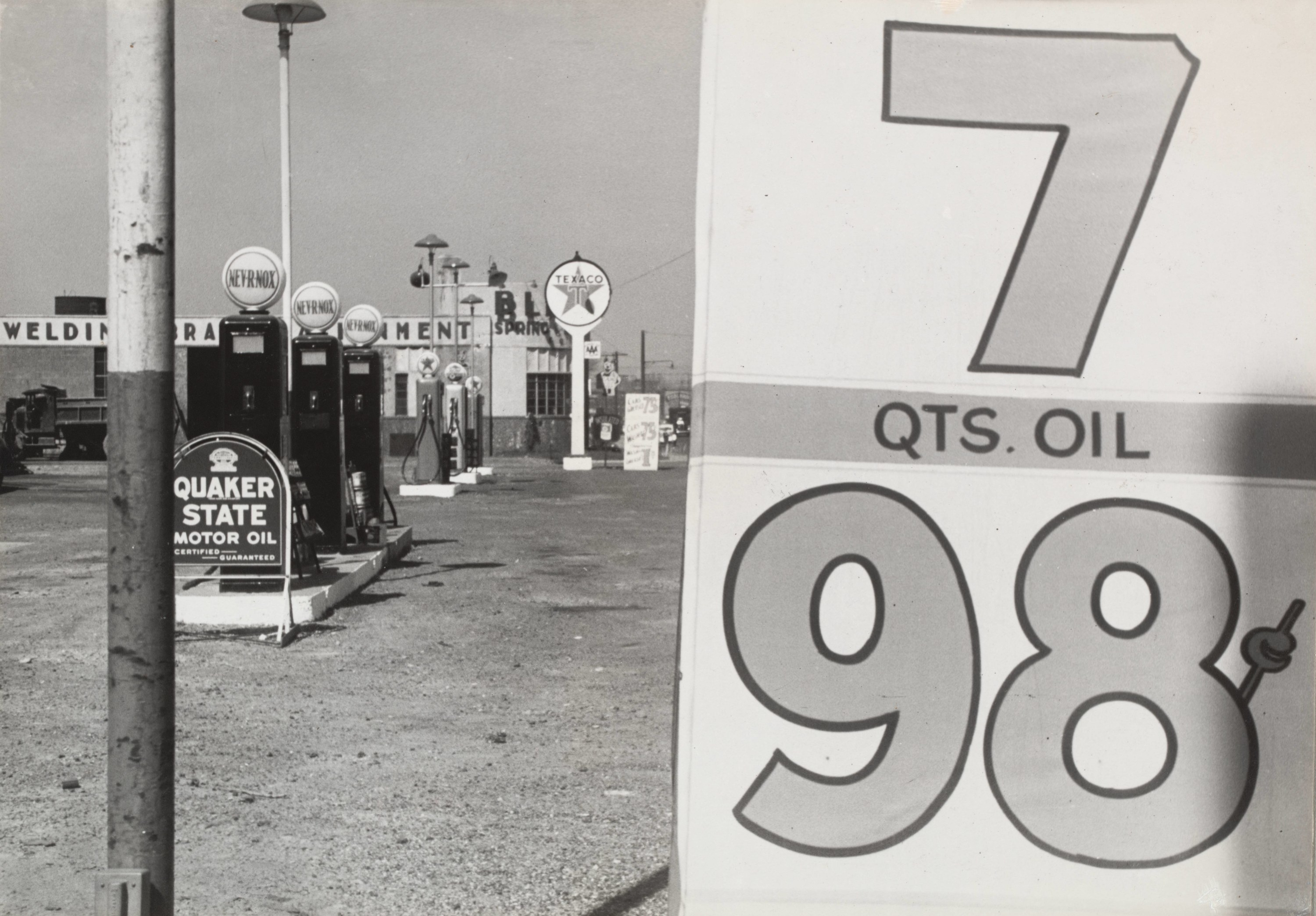 An old photograph of a gas station with a sign that reads 7 quarts of oil for 98 cents