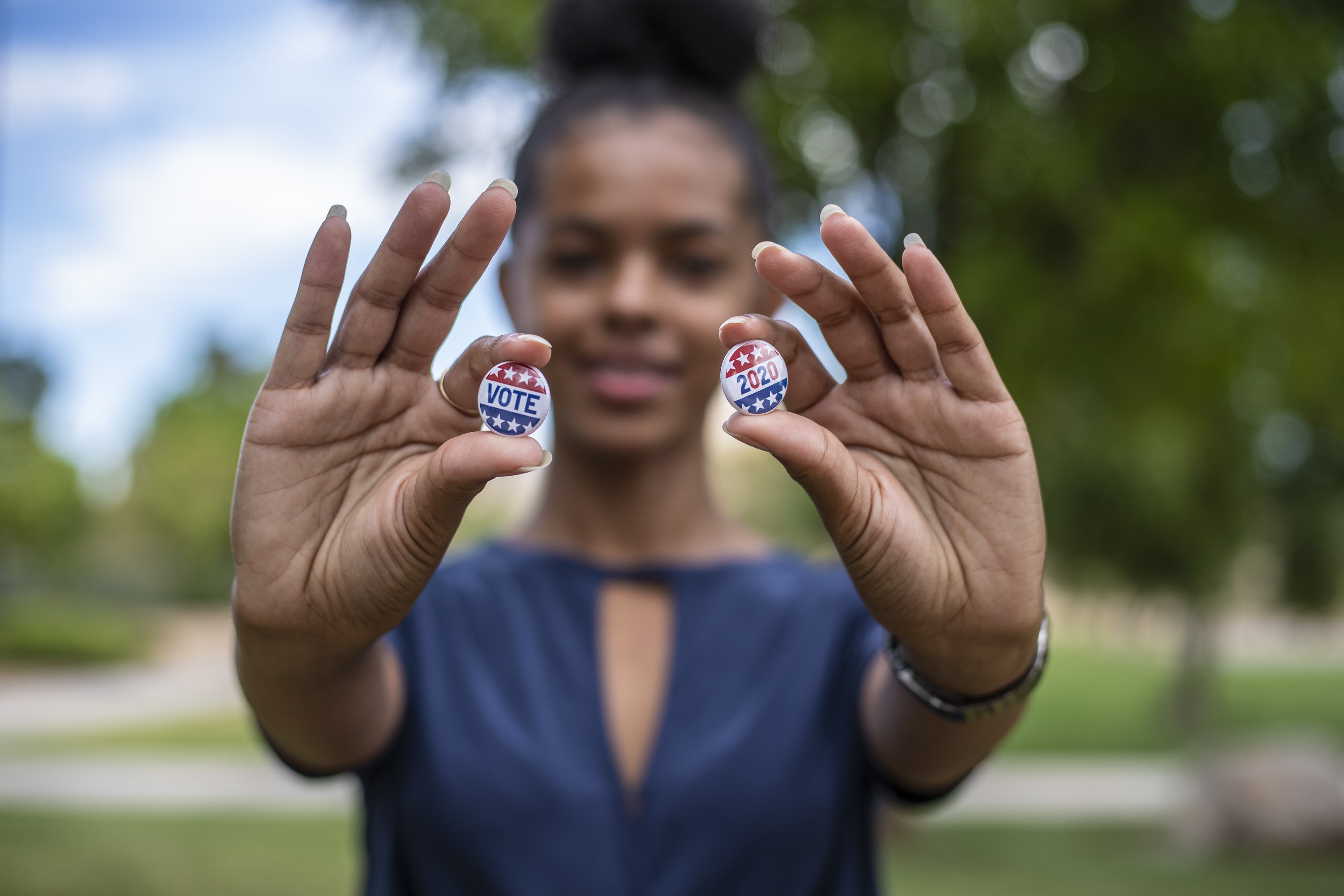 young person holding vote buttons