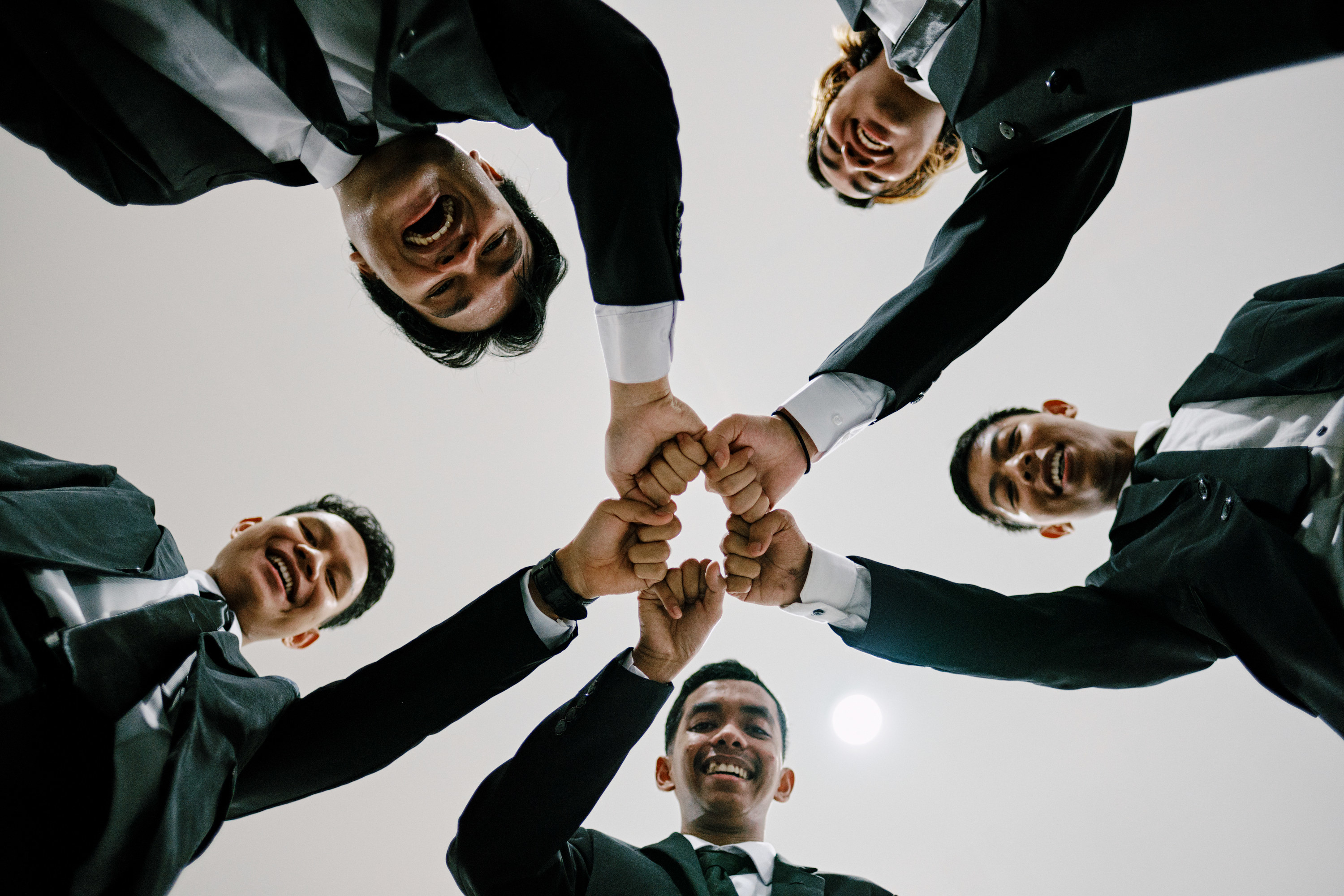 Circle of Asian American men putting hands together