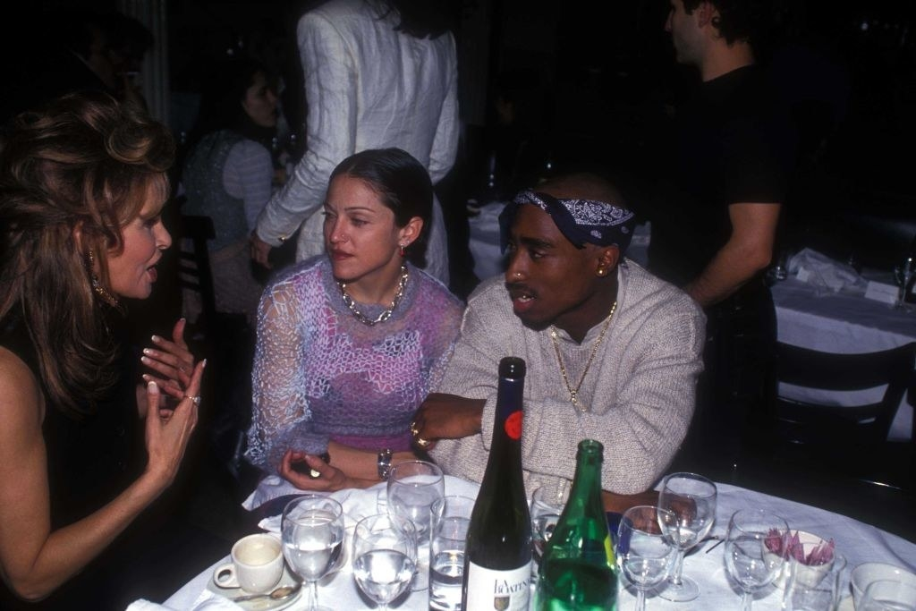 Madonna and Tupac sitting together at a dinner table at an event, 1994