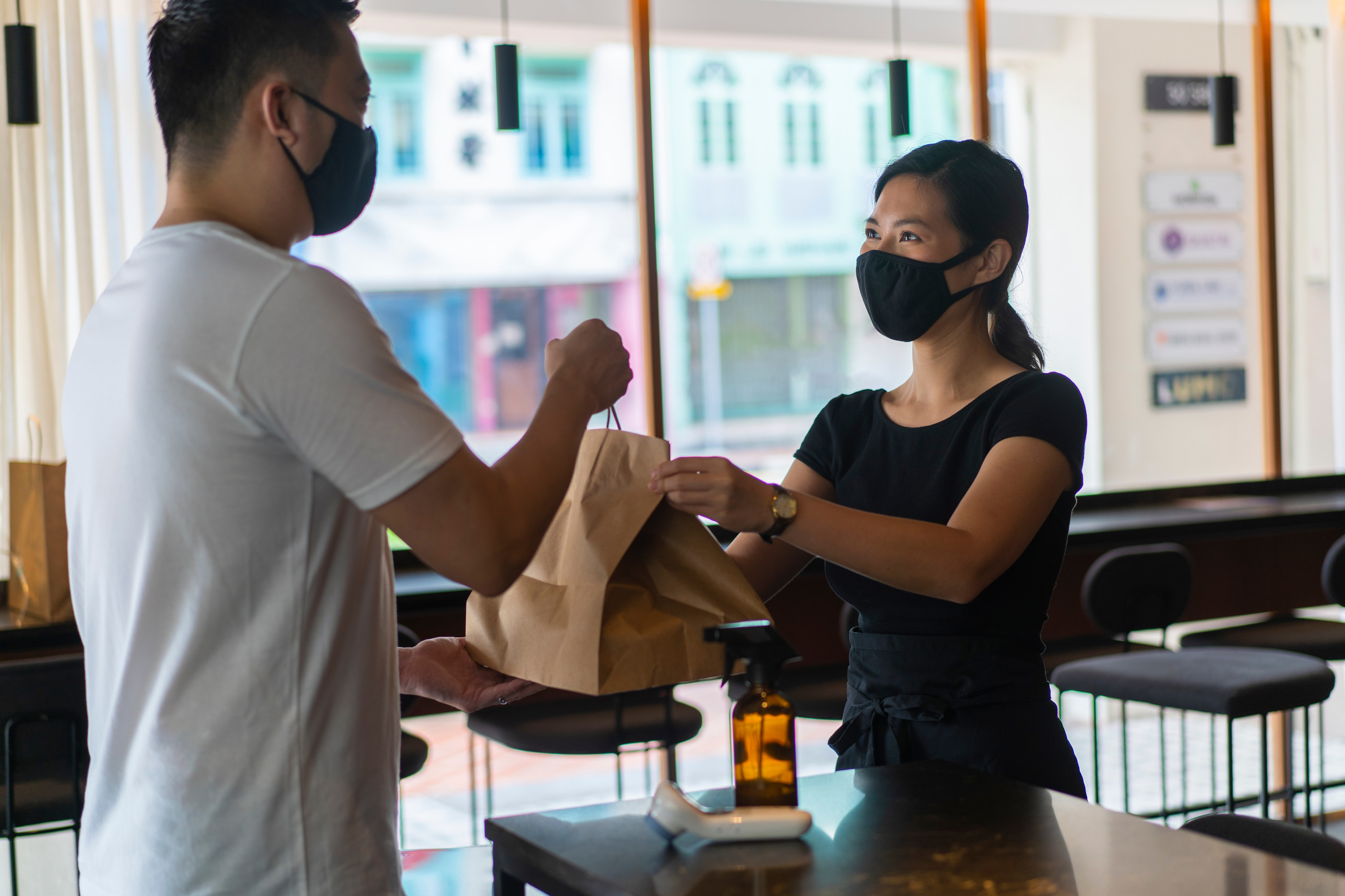 masked waitress handing takeout to customer
