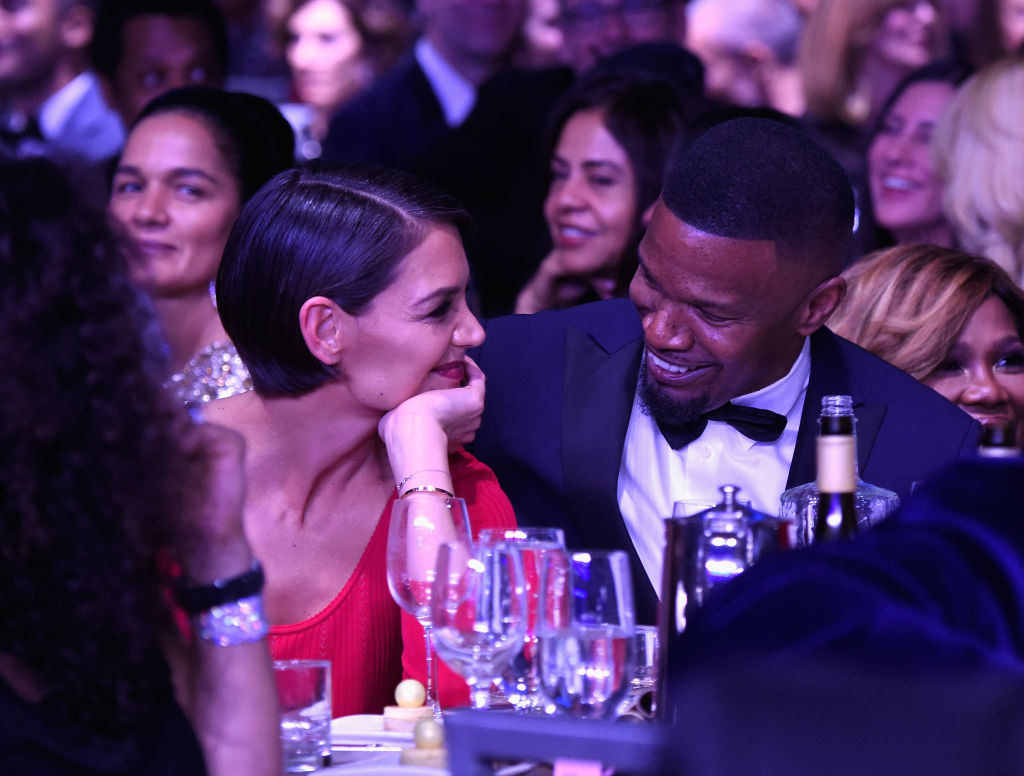 Foxx and Holmes smiling together at a dinner table at a pre-Grammy gala in 2018