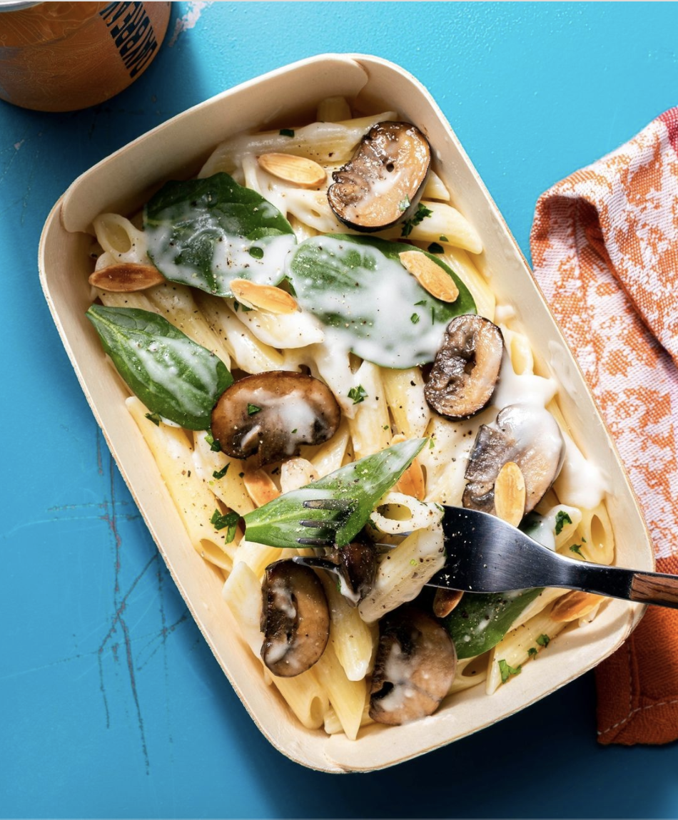 Oven baked container of creamy mushroom penne with baby spinach and almonds