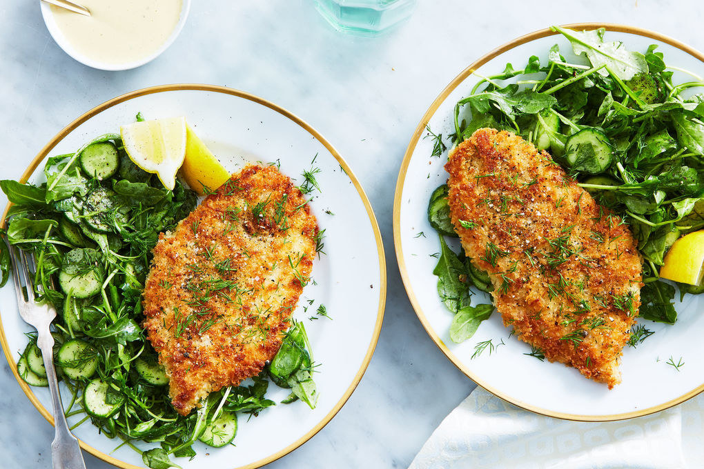 two plates of Chicken Milanese with Cucumber-Arugula Salad