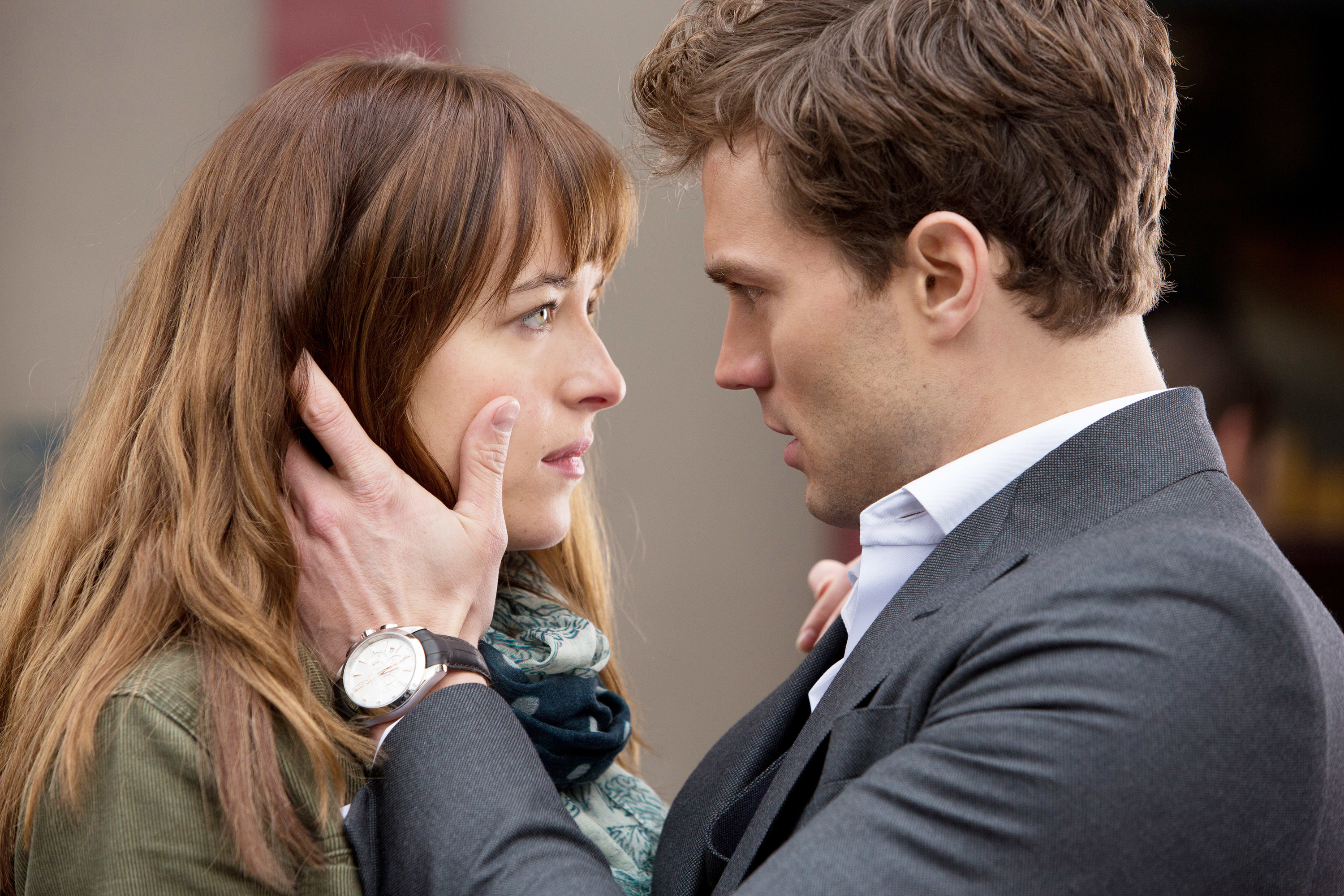 "Dakota Johnson and Jamie Dornan stare at each other intensely in ""Fifty Shades of Grey"""