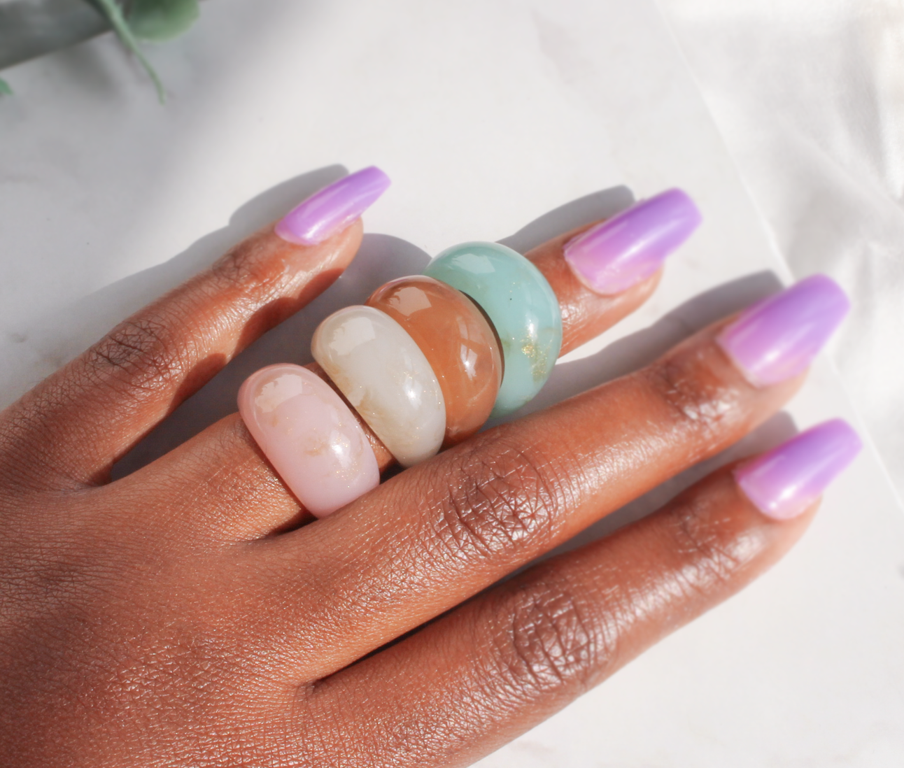 model's hand with pink, white, brown, and turquoise stone-like rings