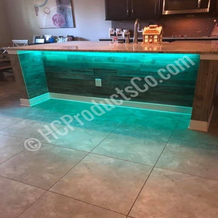 A kitchen island with green lighting below