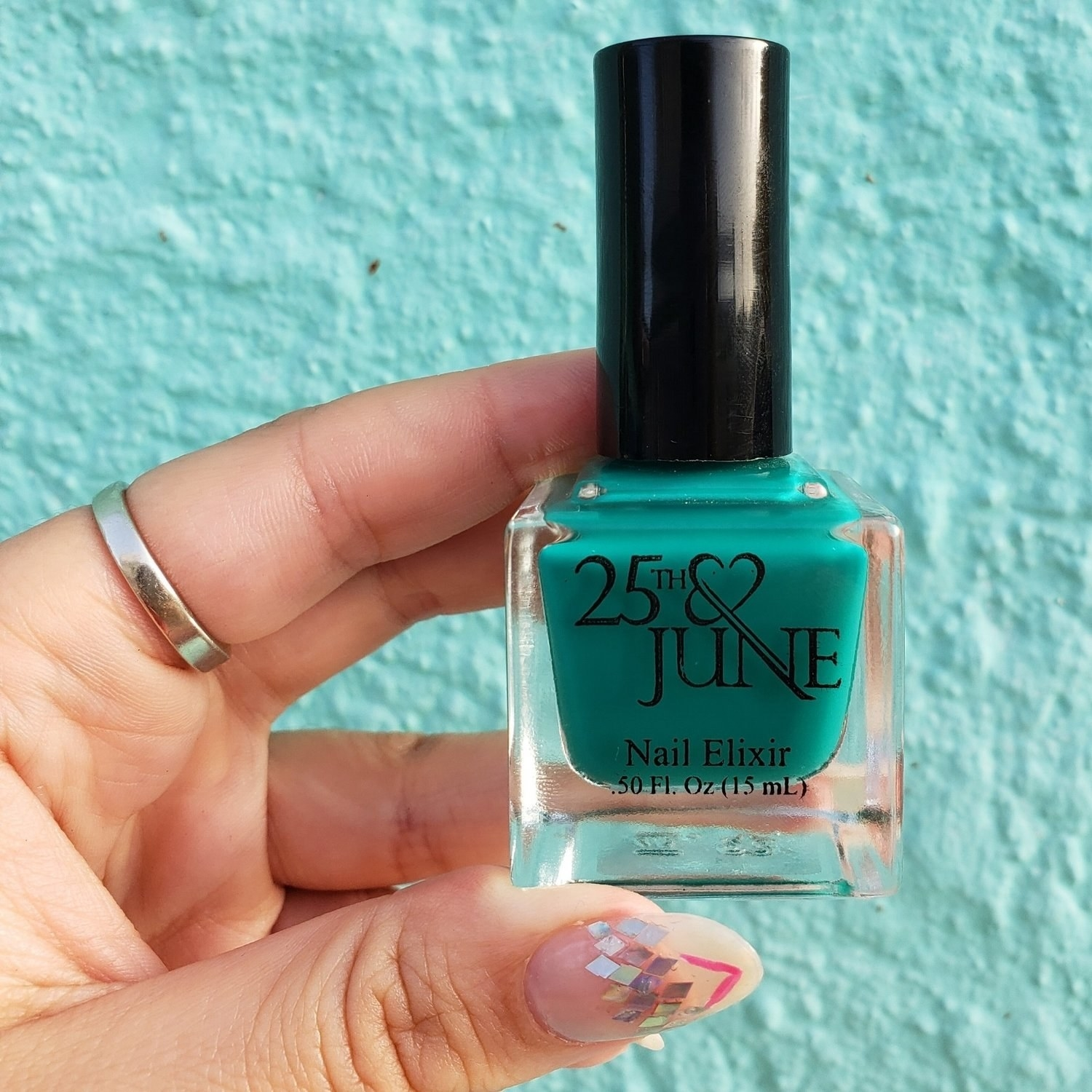 model's hand holding teal nail polish in a small glass cube bottle