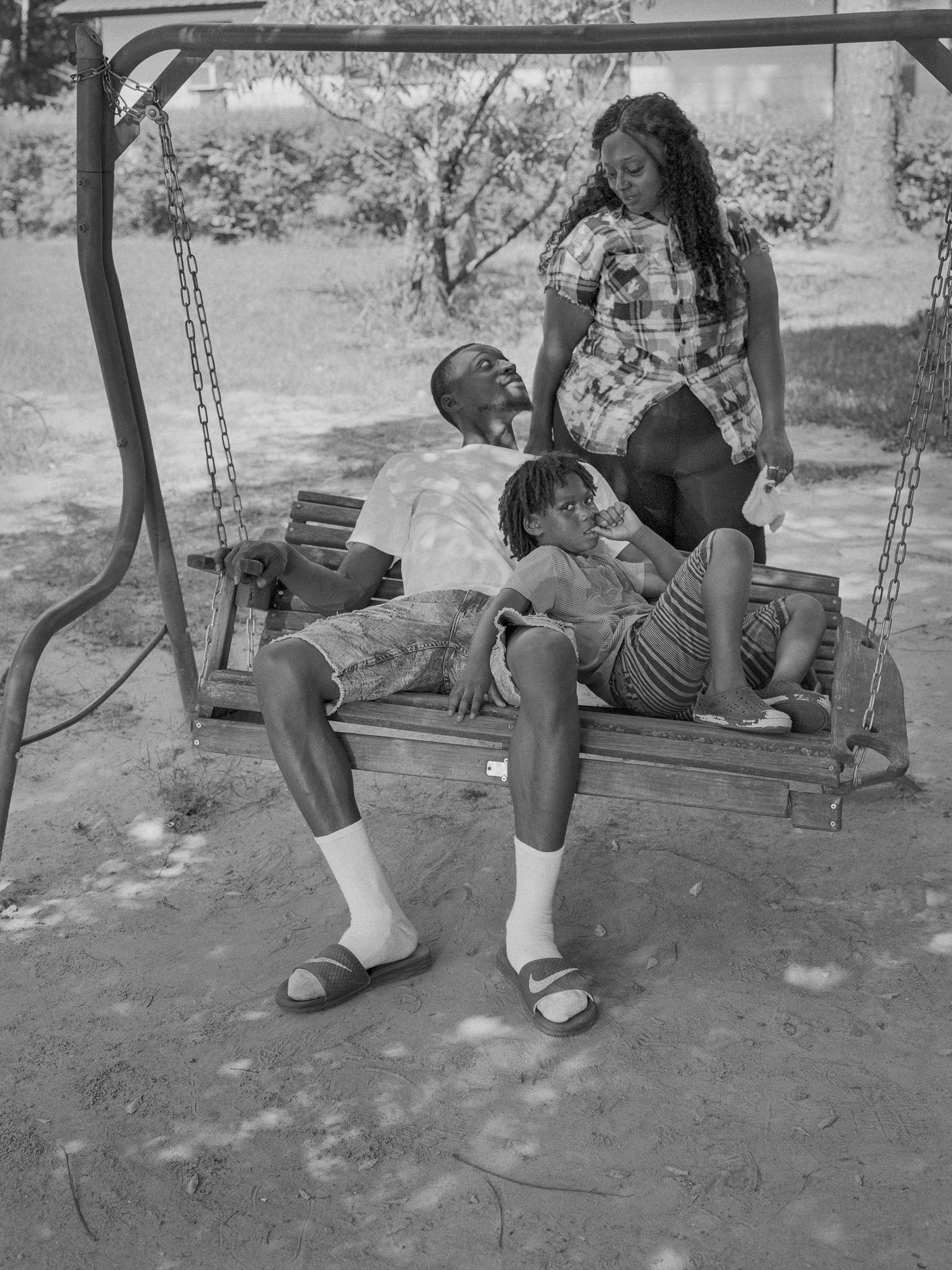 A family of a man, woman and child outside on a standing swing bench