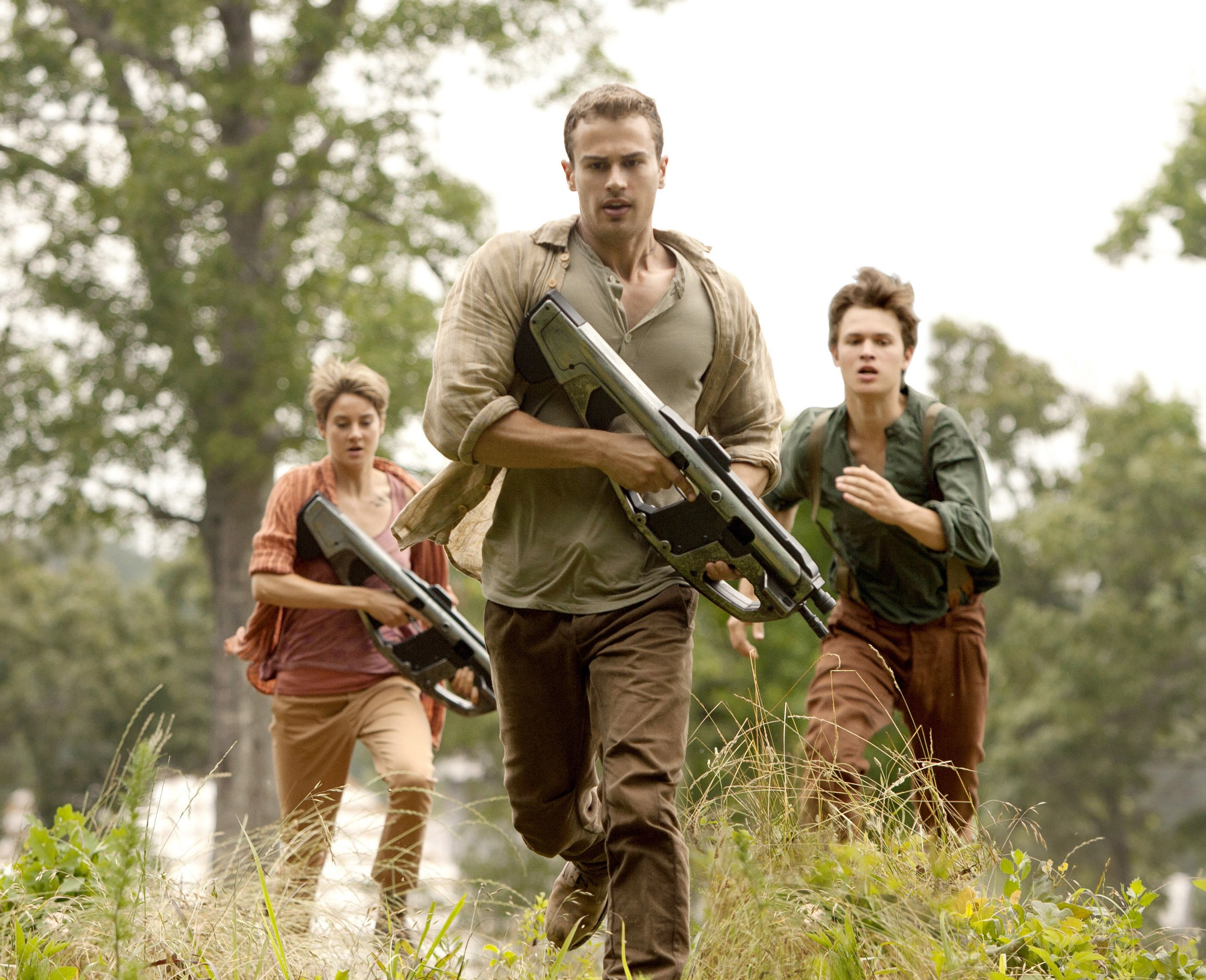 "Shailene Woodley, Theo James, and Ansel Elgort running in an action scene in ""The Divergent Series: Insurgent"""