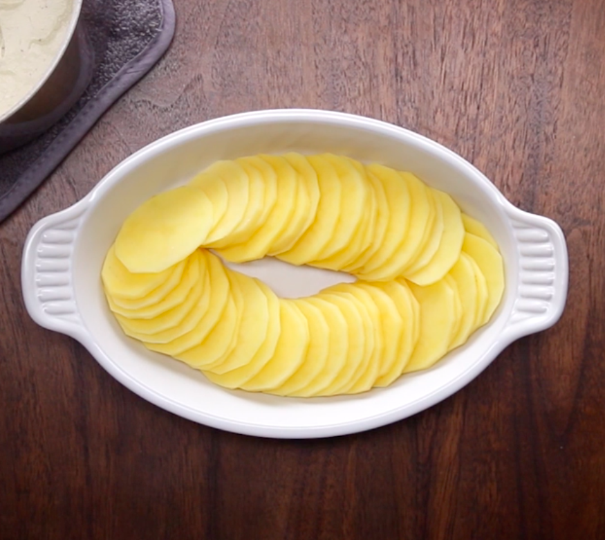 Thinly sliced potatoes in a casserole dish.