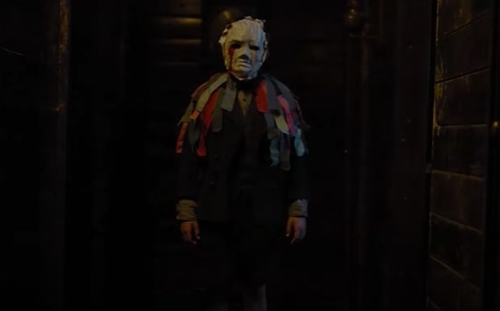 Boy in a creepy mask standing in a hallway