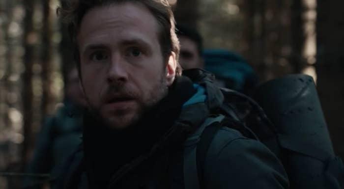 Man in the woods looking shocked