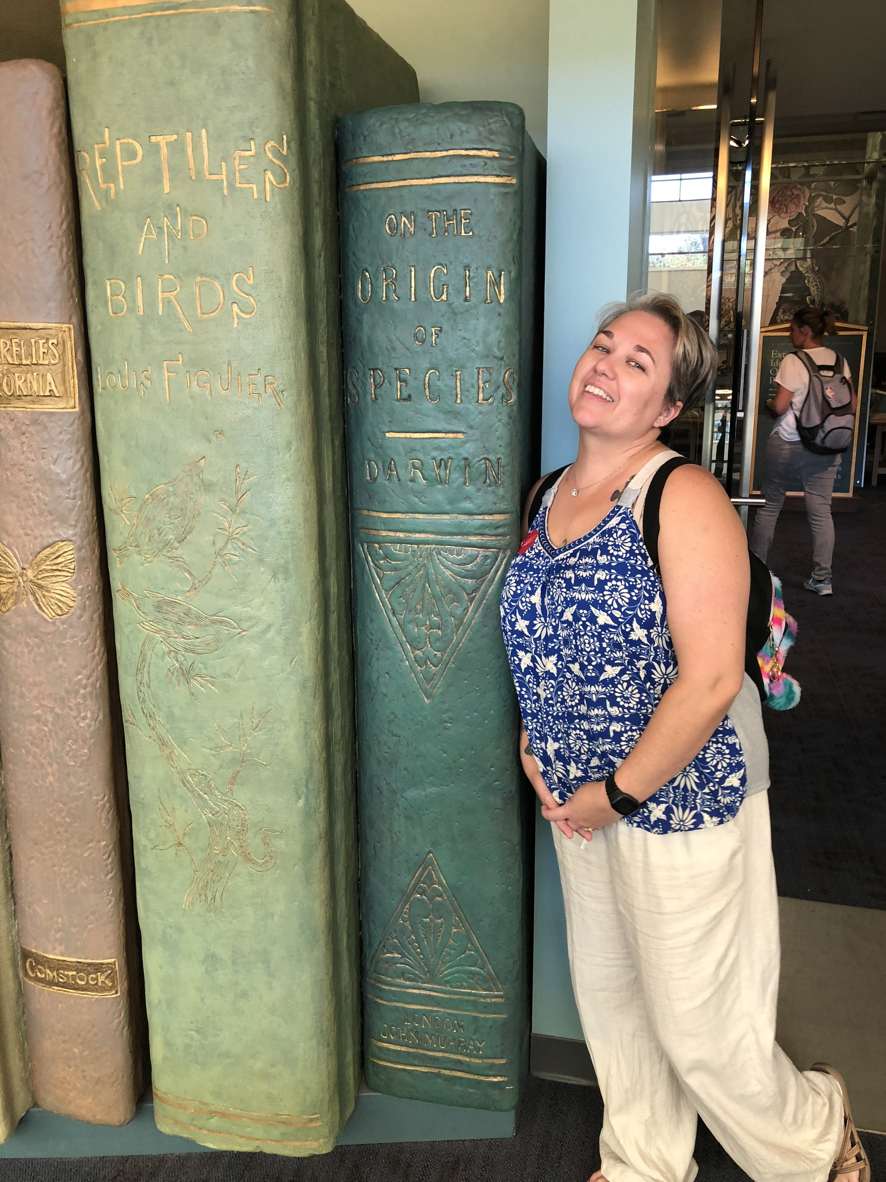 Cayce posing next to a set of giant books