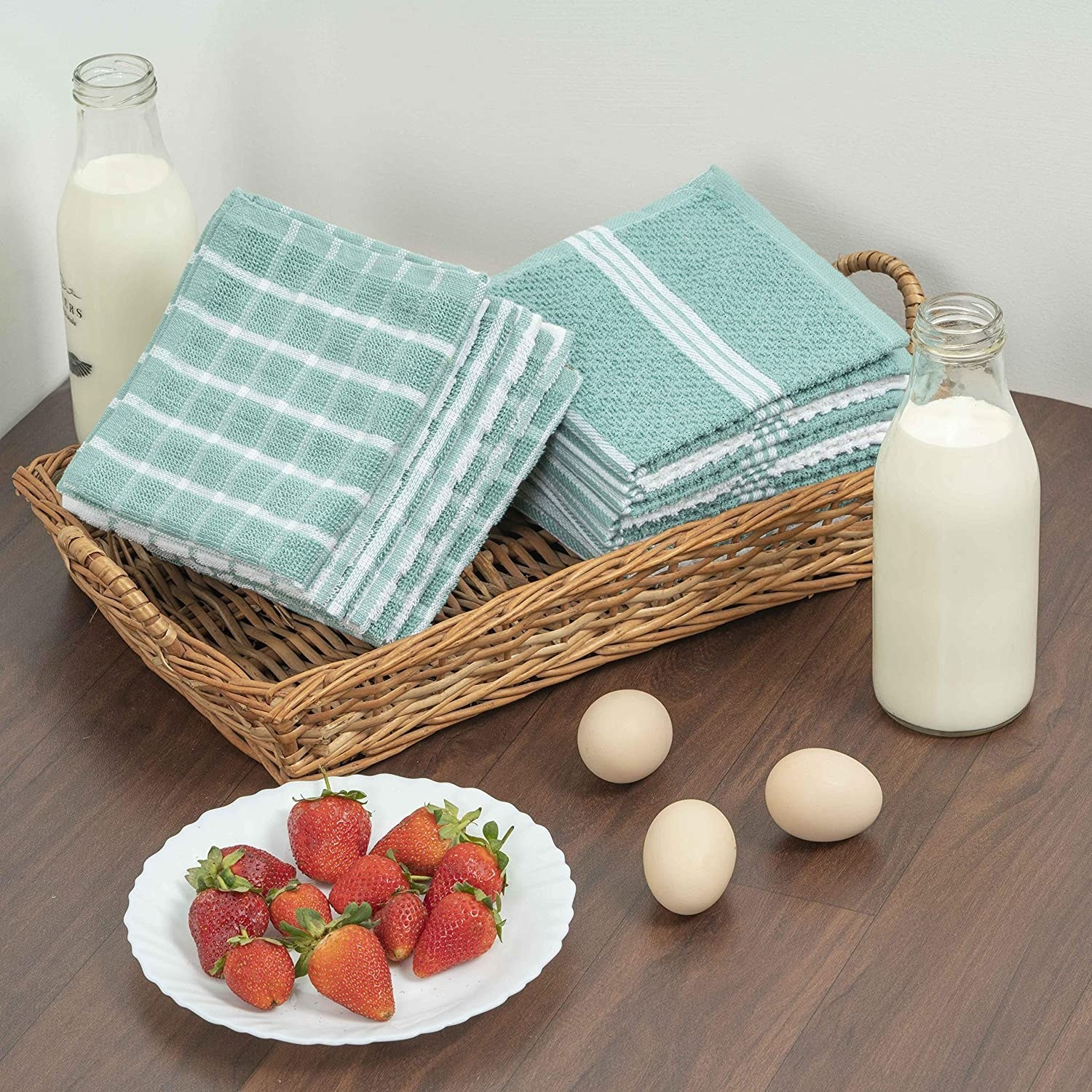 The washcloths are aqua in colour and are kept in a cane basket. There are bottles of milk, eggs, and plate of strawberries placed near it the basket.