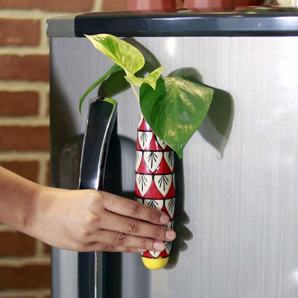 An elongated red, white, and yellow magnetic holder that's housing a plant. A person is sticking it on a fridge door.