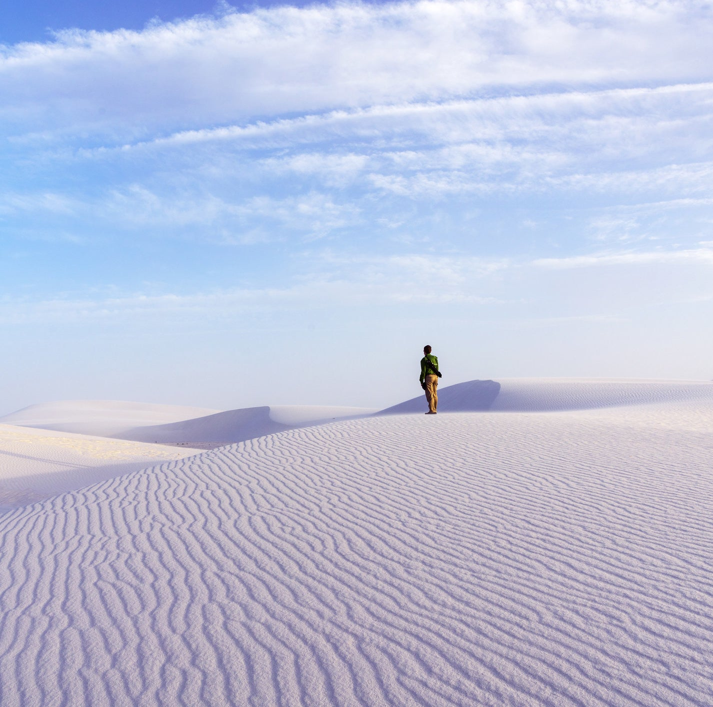 Person stands on perfectly white sand dunes