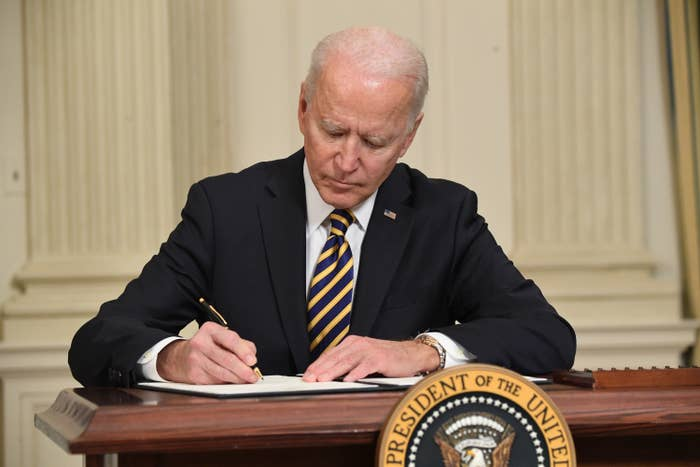 Joe Biden sits and signs a document at a desk with the presidential seal on it