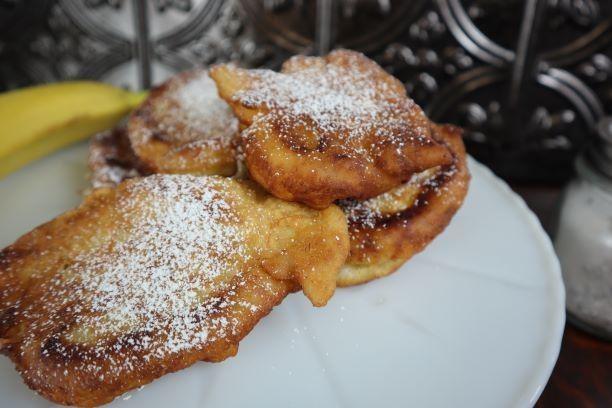 Banana fritters with powdered sugar.