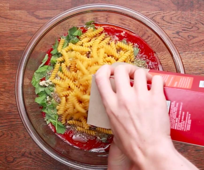 Pouring pasta into tomato sauce.