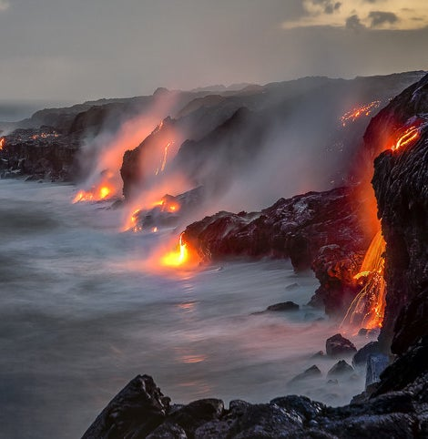 Lava flows off cliffs and into the ocean in Hawaii