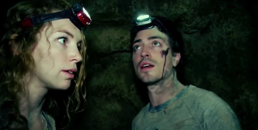 Woman and a bloodied man in a cave
