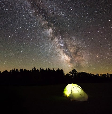 Lit tent at night beneath the Milky Way