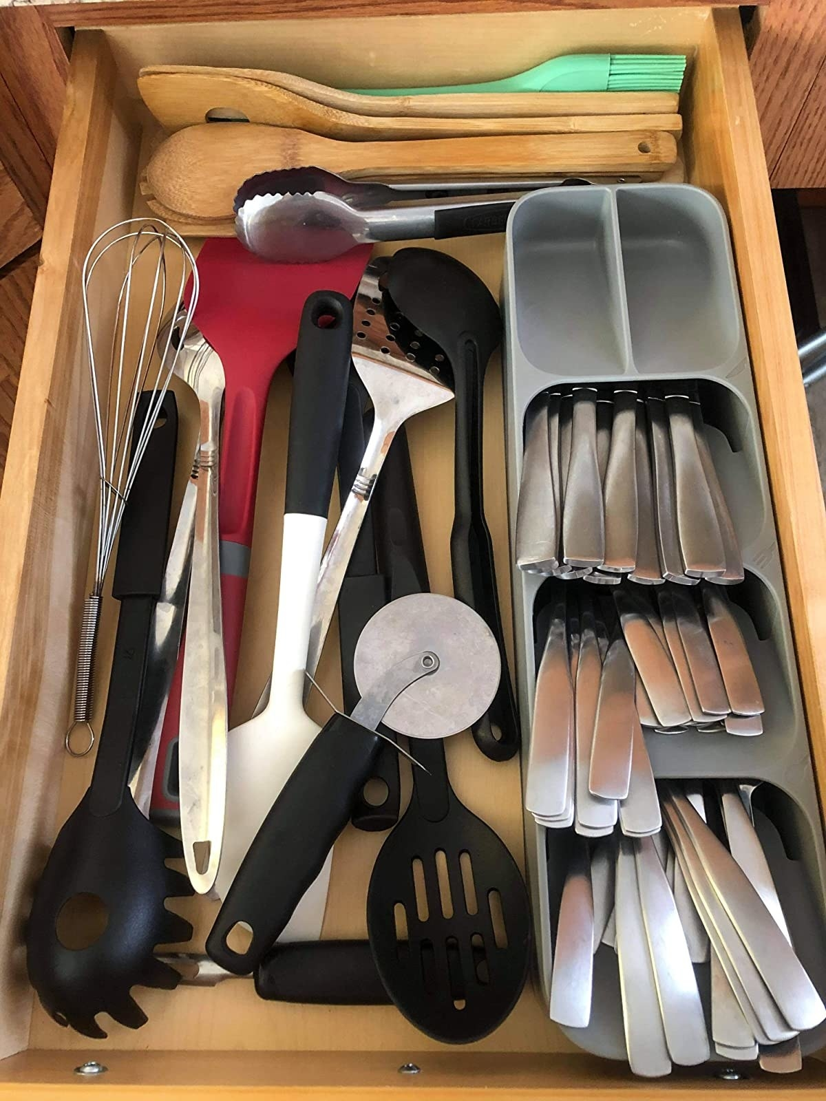 reviewer photo showing the silverware organizer along with several other kitchen utensils in the drawer