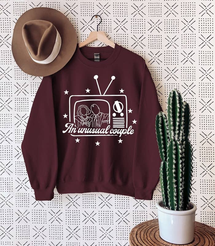 The sweater hung up next to a cactus and hat