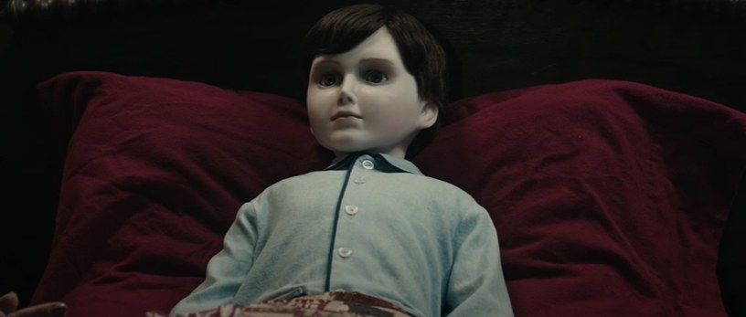 A doll laying in bed.