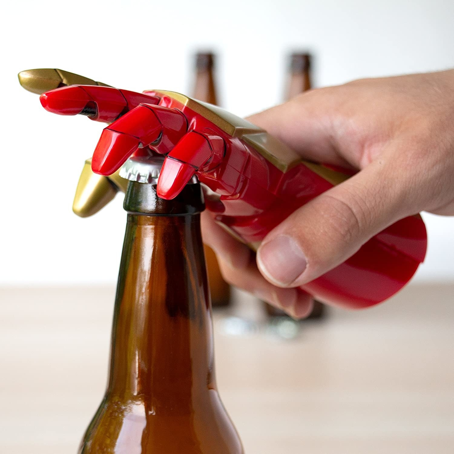 A person using the bottle opener to crack open a beer