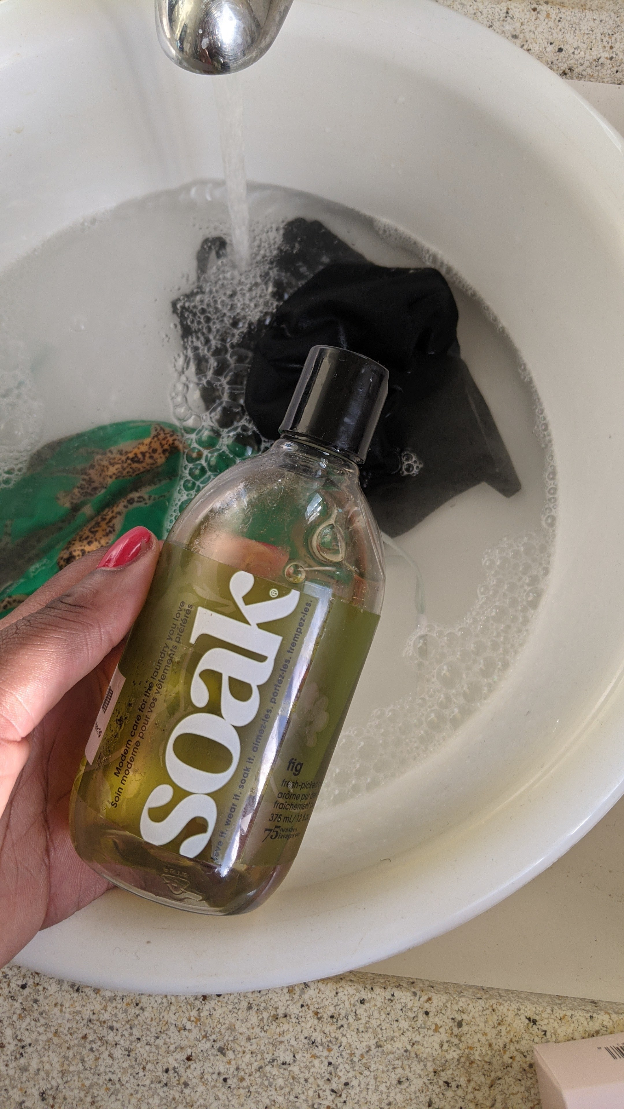 A person holding a small bottle of laundry detergent over a basin filled with water