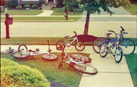 An old photo of a bunch of bikes scattered on a front lawn