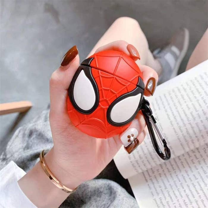 A person holding the Spiderman case above a book