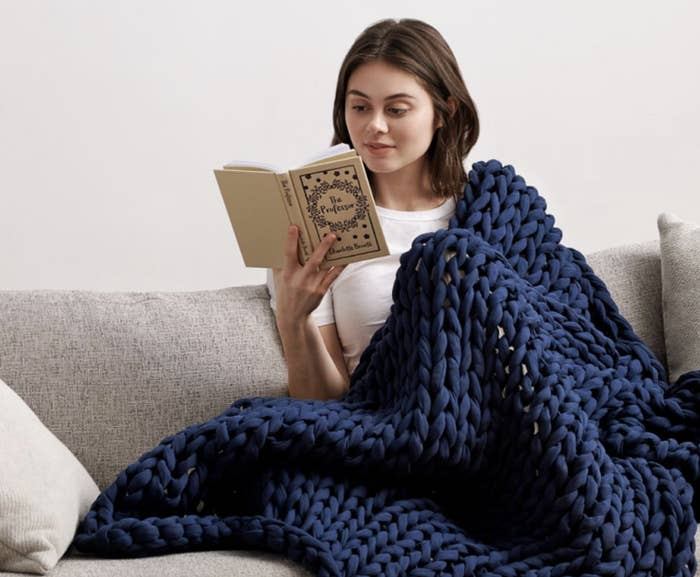 model reading a book while covered with the Bearaby weighted blanket