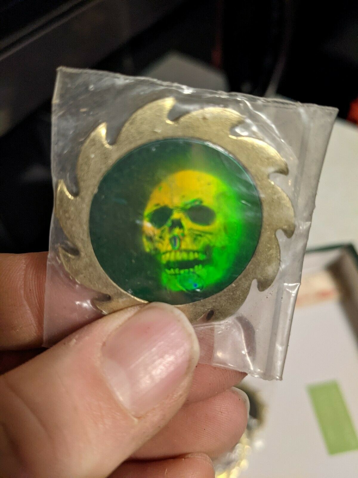 An old pog slammer with a skull on it and serrated edges like a saw