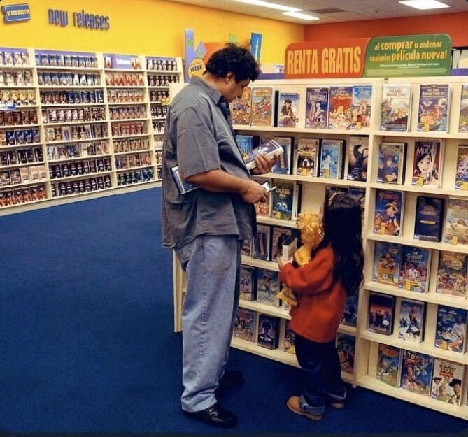 A father and daughter shopping for a movie to rent at blockbuster