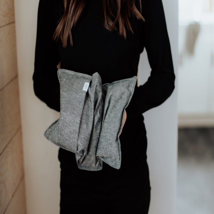 A model holding the therapy pack with a gray chambray outer slip