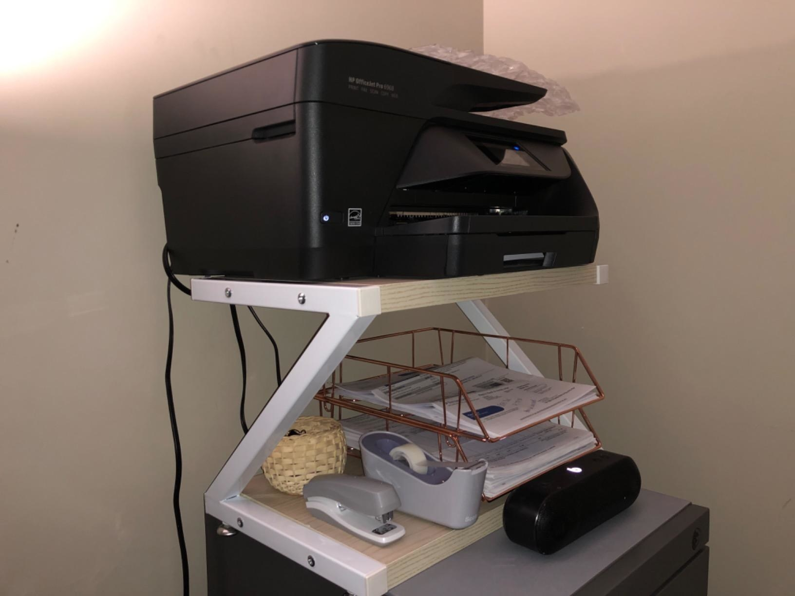 reviewer image of a big printer on the top shelf of the printer desktop stand and office supplies on the lower shelf