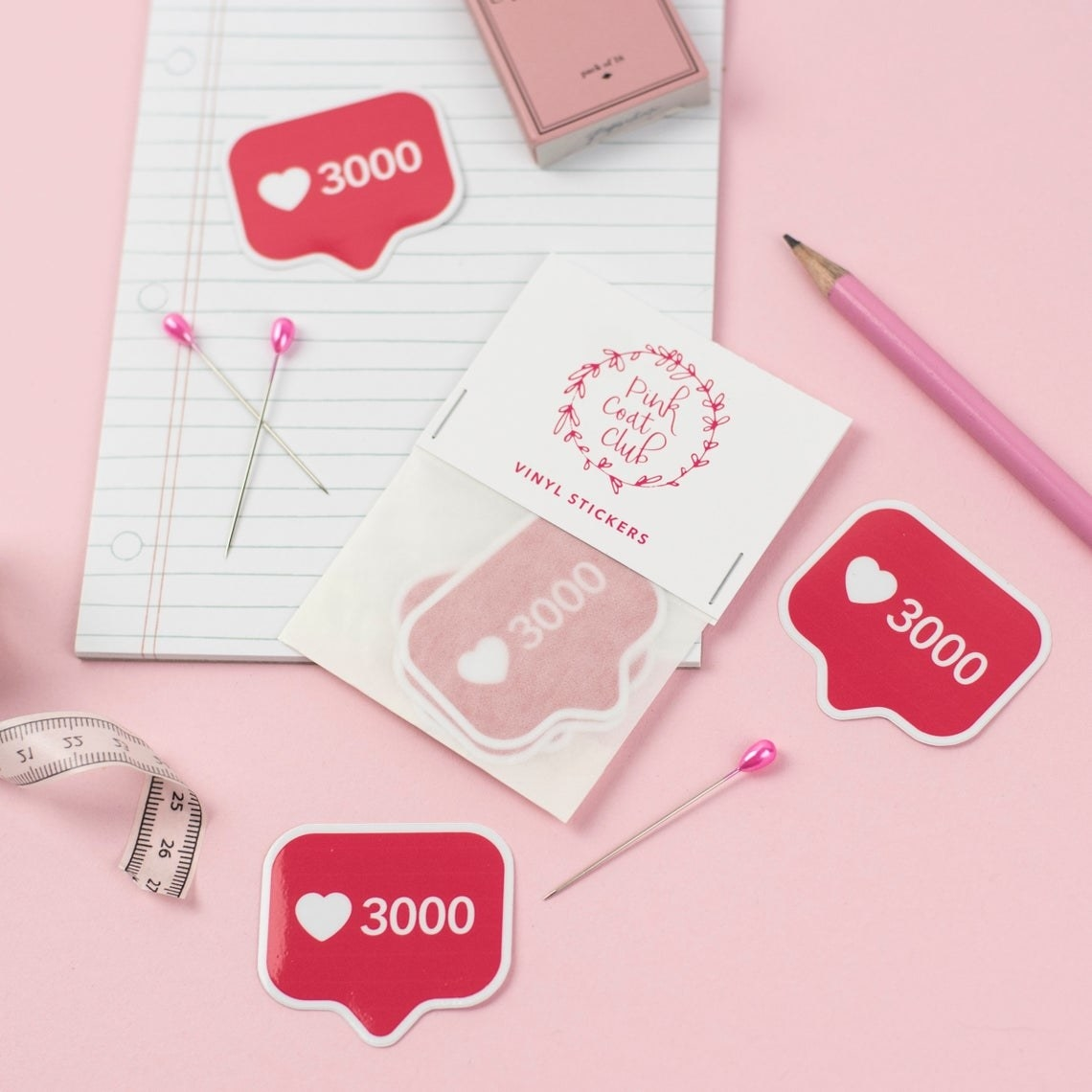 The stickers surrounded by a notepad, pencils, and pins