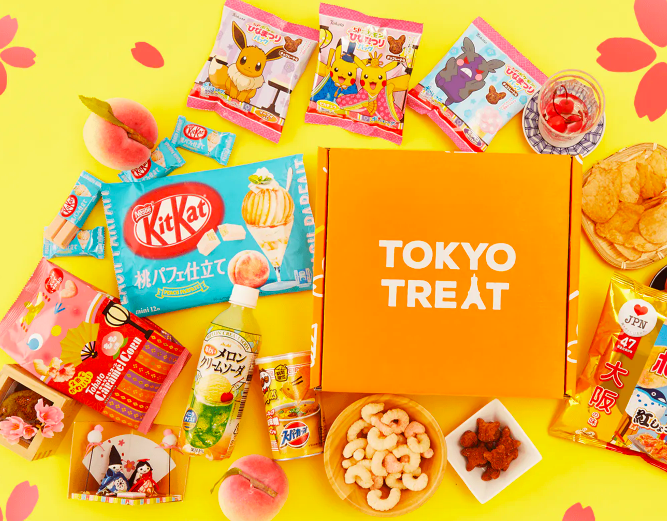 Orange box surrounded by several different types of candy, treats, drinks, and other snacks
