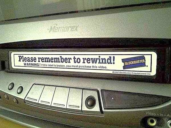 "An old blockbuster rental tape sticking out of a VCR that reads, ""Please remember to rewind"""