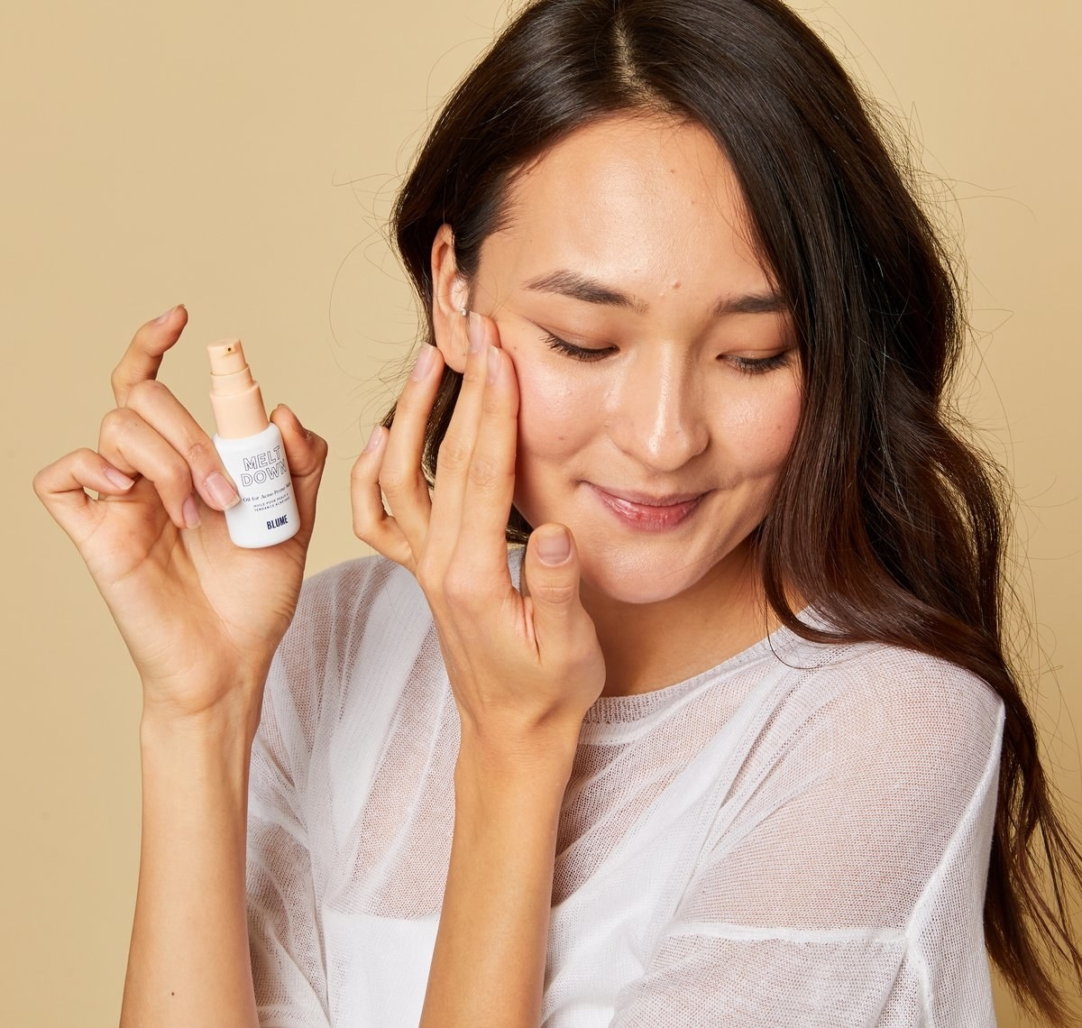 model holding a bottle of the acne oil and applying some to their face