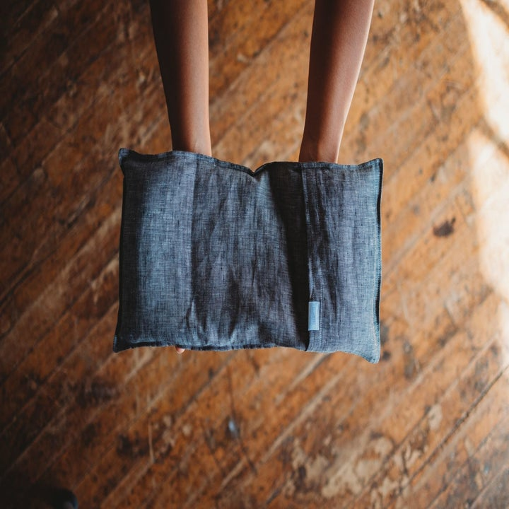A pair of hands holding the rectangular-shaped therapy pack with a chambray outer slip