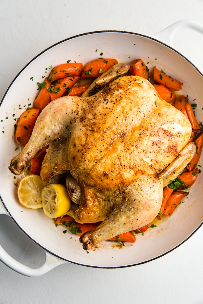 A whole roast chicken over carrots.