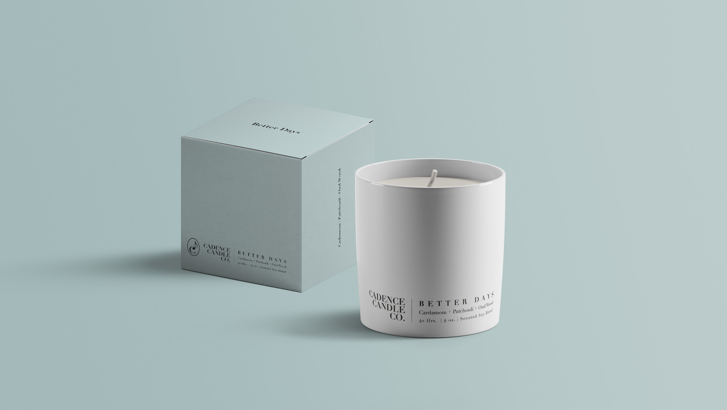 a white candle that says better days on it next to a pale blue box