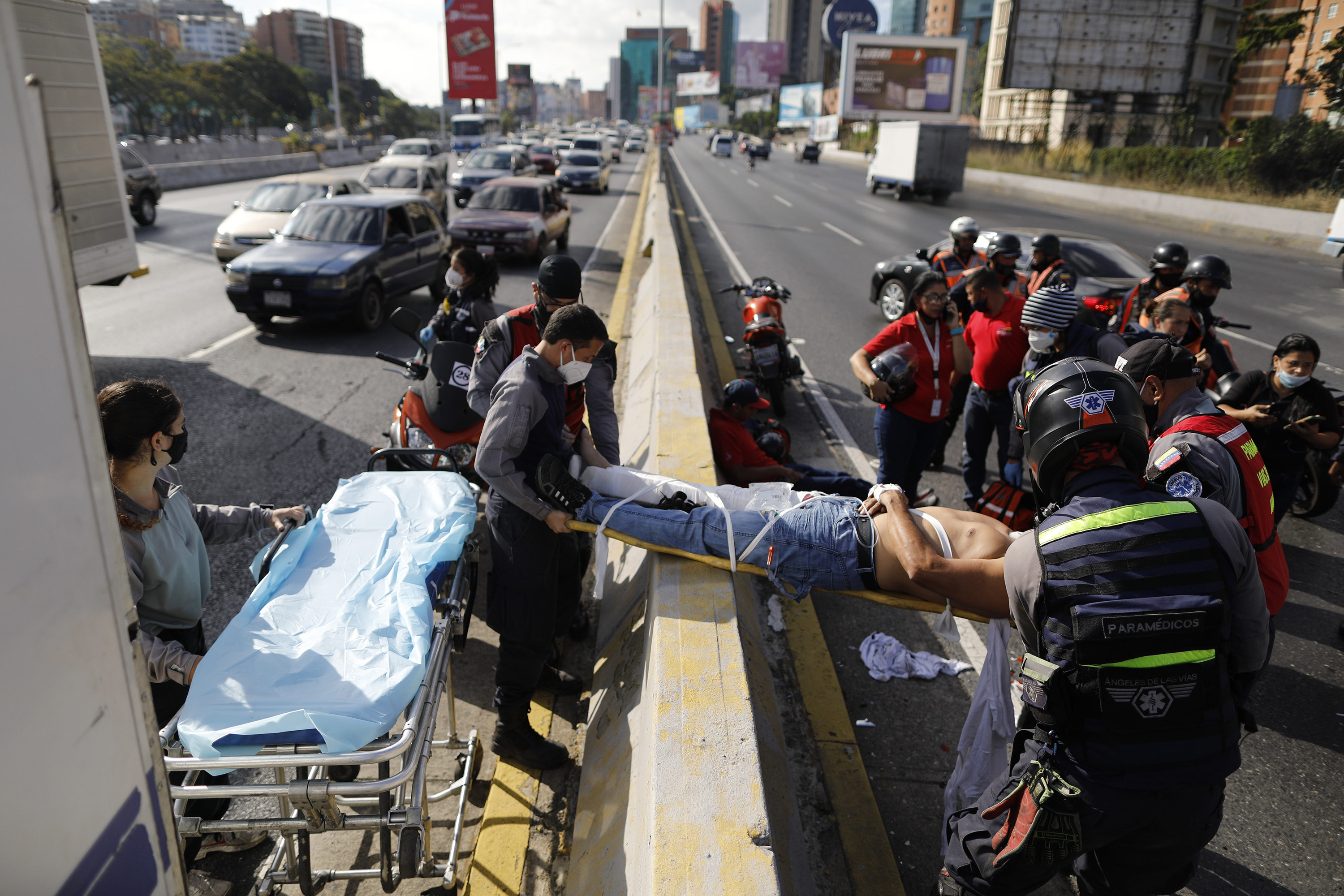 a group of people moving a man on a stretcher onto a gurney in the middle of a highway