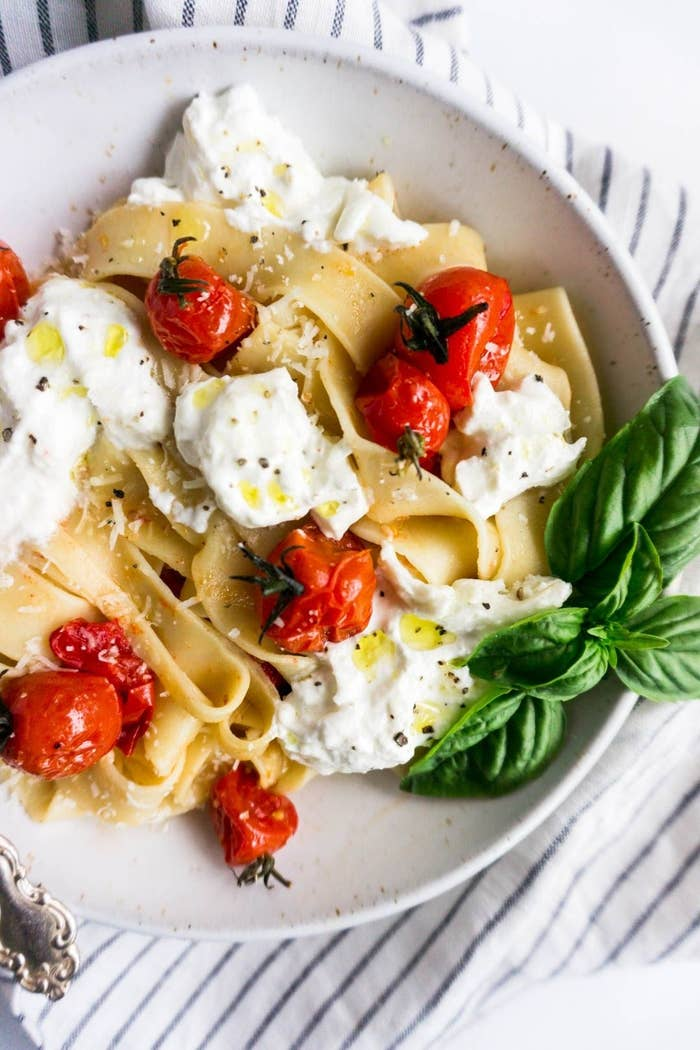 A plate of pasta with cherry tomatoes, burrata, and basil.